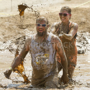 BOISE/IDAHO AUGUST 25: Runners in The Dirty Dash playing in the mud. One runner is splashing her friend. This took took place in Boise, Idaho on August 25, 2012 - Shot Your show