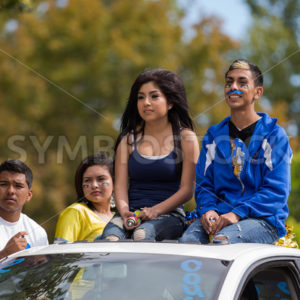 CALDWELL, IDAHO/USA – SEPTEMBER 27:Four unidentified students sitting on the top of a car at the Caldwell High School Homecoming parade on September 27, 2013 - Shot Your show