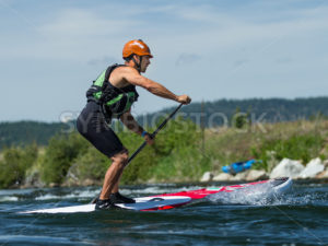 CASCADE, IDAHO/USA - JUNE 21, 2014: Stand up Paddle boarder  driving to the finish at the Payette River Games - Shot Your show