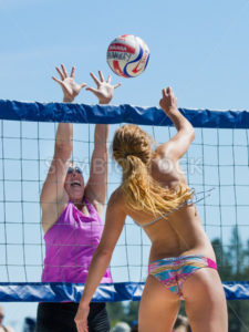 CASCADE, IDAHO/USA - JUNE 21, 2014: Unidentified woman trying to spike the ball while another woman attemps a block at the Payette River Games in Cascade, Idaho - Shot Your show