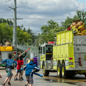 EAGLE/IDAHO – JUNE 9: Children are trying to squirt firemen sitting on top of their firetrucks during the Eagle Fun Days in Eagle, Idaho on June 9th, 2012 - Shot Your show