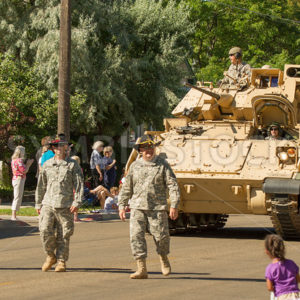 MIDDLETON, IDAHO – JULY 4: US army walking down the street in front of a M2 in Middleton, Idaho 2012 - Shot Your show