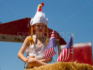 MIDDLETON, IDAHO – JULY 4: Unidentified child sitting on some hay with some american flags during the 4th of july parade 2012 in Middleton, Idaho - Shot Your show