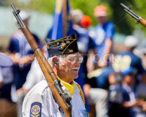 Man walking during a parade holding his gun - Shot Your show
