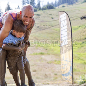 BOISE, IDAHO/USA – AUGUST 11, 2013: Father holding his son near the finish line at The Dirty Dash in Boise, Idaho - Shot Your show