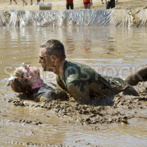 BOISE, IDAHO/USA – AUGUST 11, 2013: Man and woman getting ready to kiss in the mud at the Dirty Dash in Boise, Idaho - Shot Your show