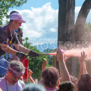 BOISE, IDAHO/USA – JUNE 22: Unidentified man sprays the crowd with burst of color at The Color Me Rad 5k in boise on June 22, 2013 - Shot Your show